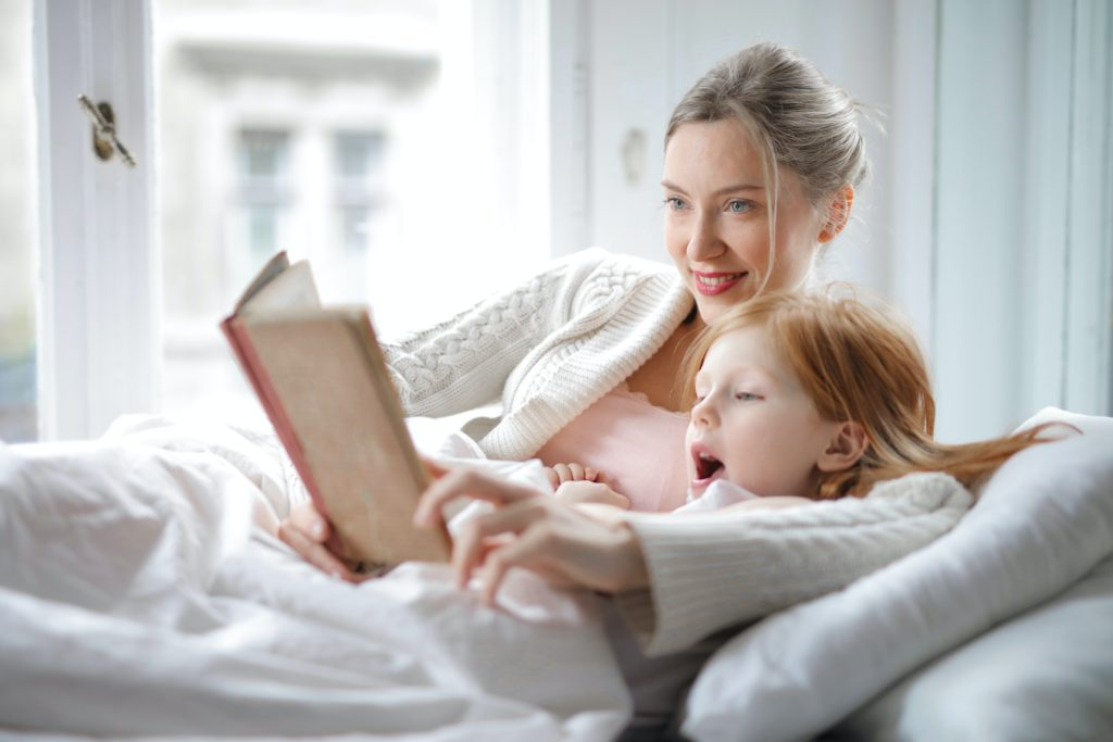 Story book being read to daughter by mother